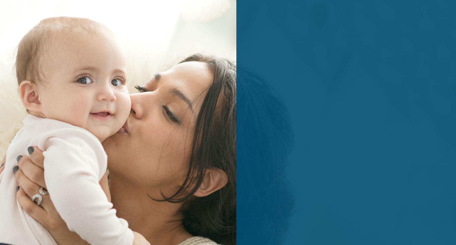 Joven madre con bebé sonriente y besándolo en la mejilla