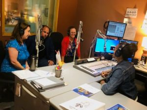 Three adults wearing headphones sit facing an interviewer in a radio control room full of micrphones, computer screens, and recording equipment.