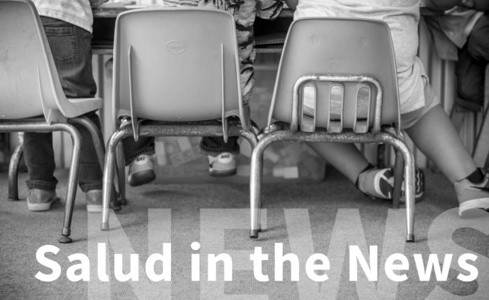 "Backs of three young children seated at a table with words ""Salud in the News"" below their image."