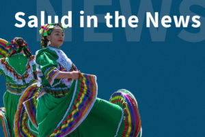 "Two Latina women, wearing colorful traditional Mexican dresses, dancing with words ""Salud in the News"" behind their image."